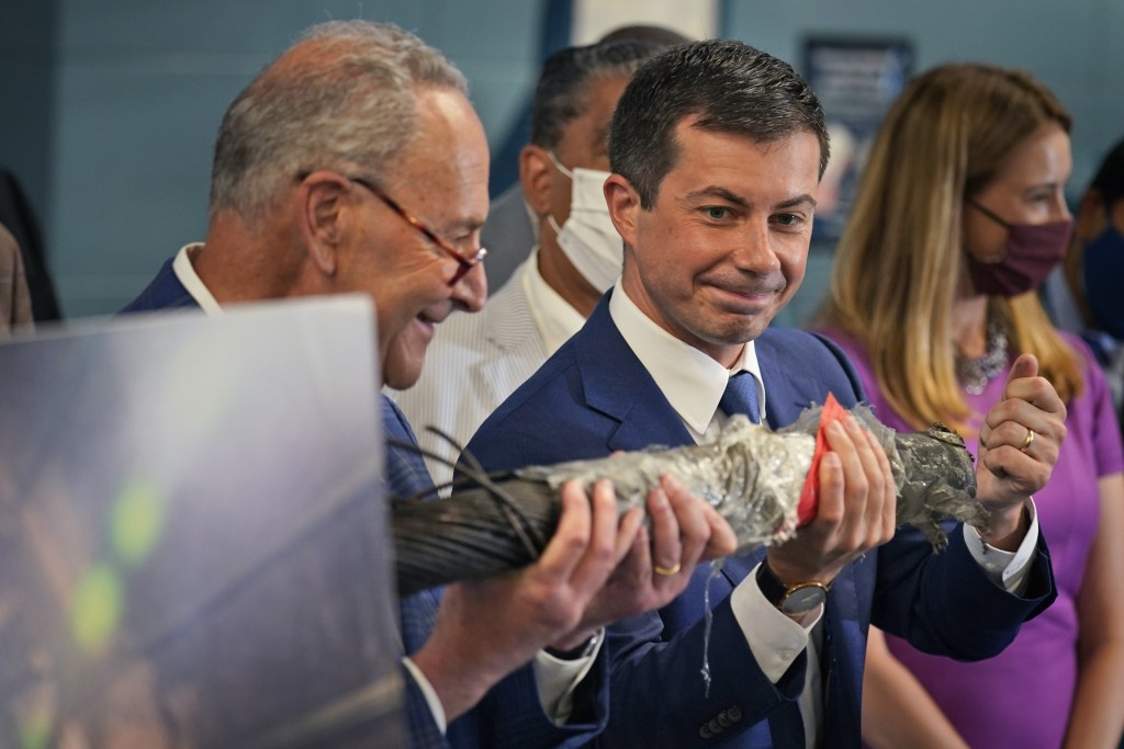 Secretary of Transportation Pete Buttigieg, right, and Sen. Chuck Schumer, D-N.Y., hold a decaying piece of a rail tunnel while they speak during a ne...