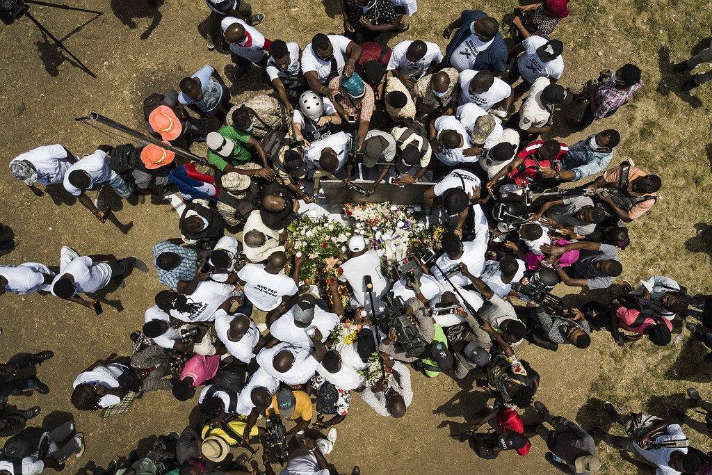 Members of the press gather around supporters of slain President Jovenel Moise bringing flowers, cigars, candles and prayer to create a memorial outsi...