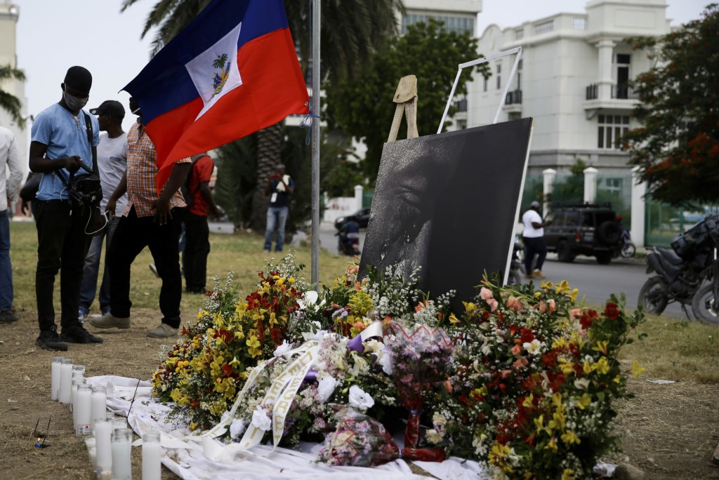A photo, altered to show the slain Haitian President Jovenel Moise weeping, and a national flag make up part of a memorial outside the presidential pa...