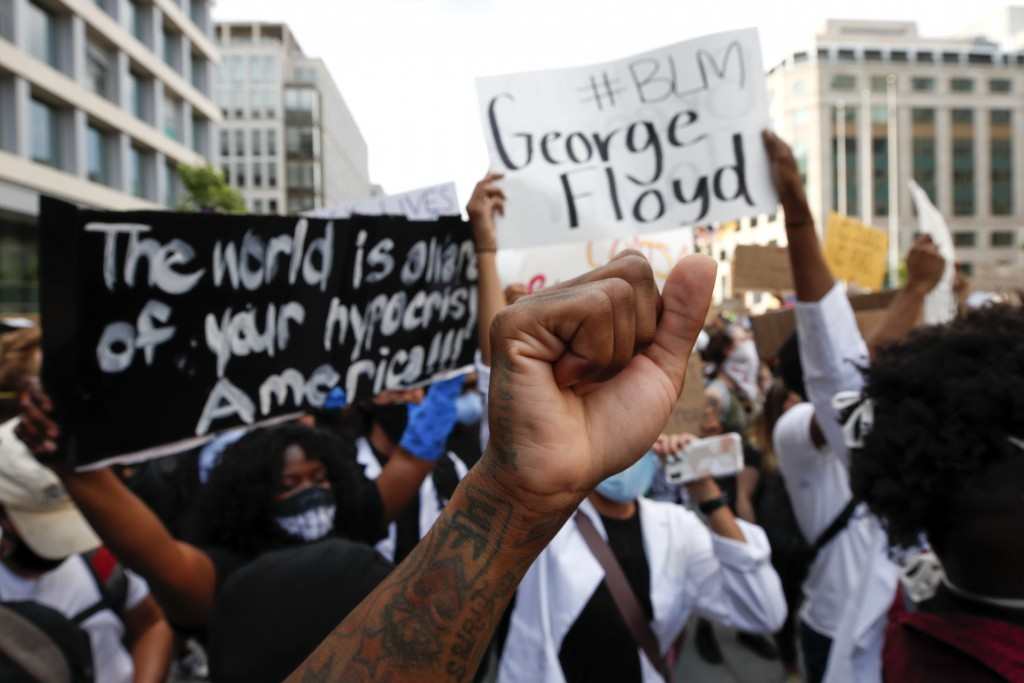 FILE - In this June 3, 2020, file photo, demonstrators gather near the White House in Washington to protest the death of George Floyd. A report releas...