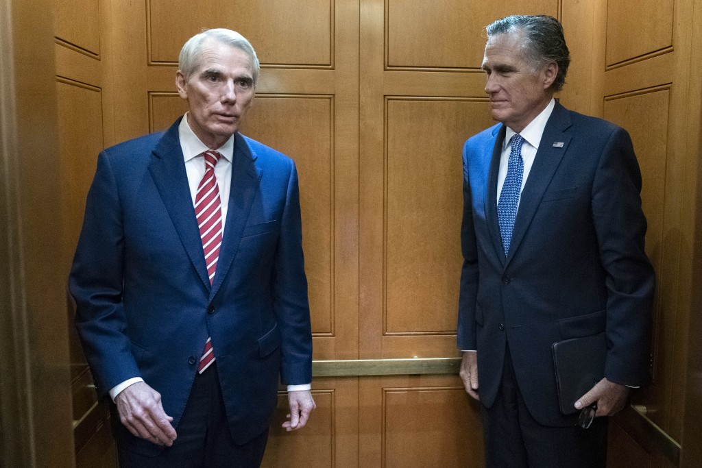 Sen. Rob Portman, R-Ohio, left, accompanied by Sen. Mitt Romney, R-Utah, leave in the elevator after a closed door talks about infrastructure on Capit...