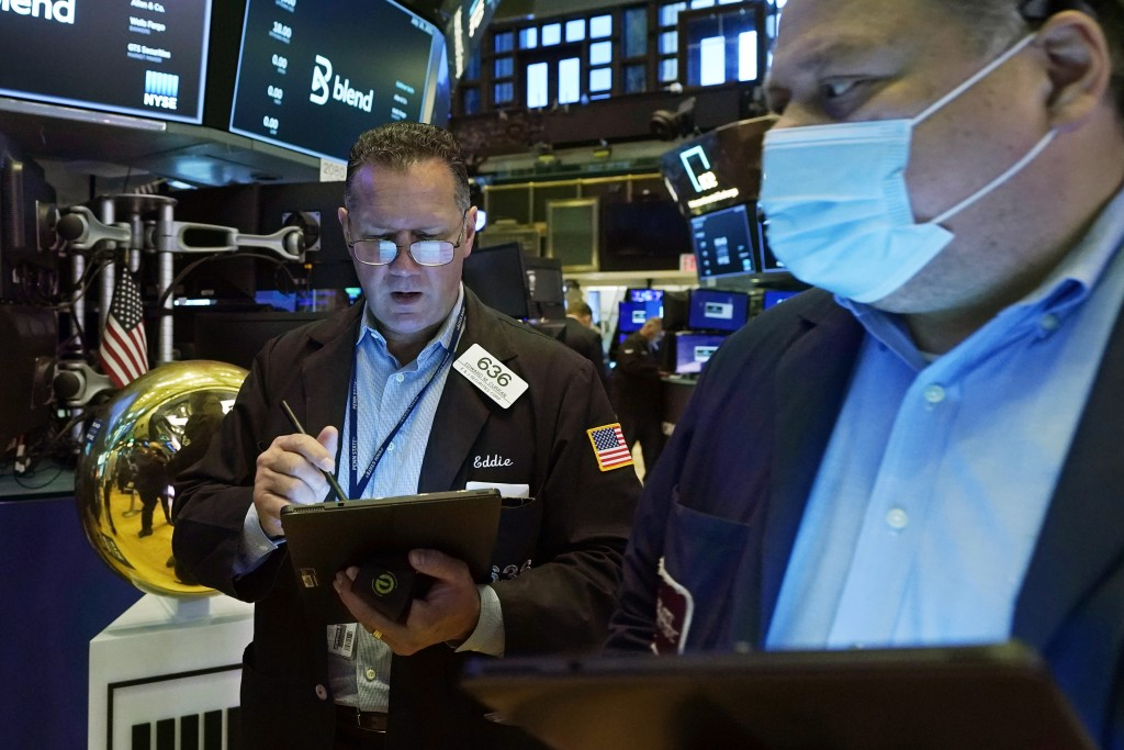 Trader Edward Curran, left, works on the floor of the New York Stock Exchange, Friday, July 16, 2021. Stocks are off to a slightly higher start on Wal...