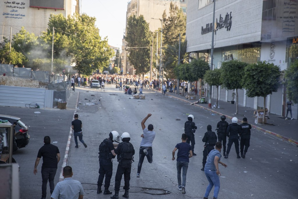 Palestinian riot police and plainclothes security officers clash with protesters following a demonstration against the death of Nizar Banat, a critic ...