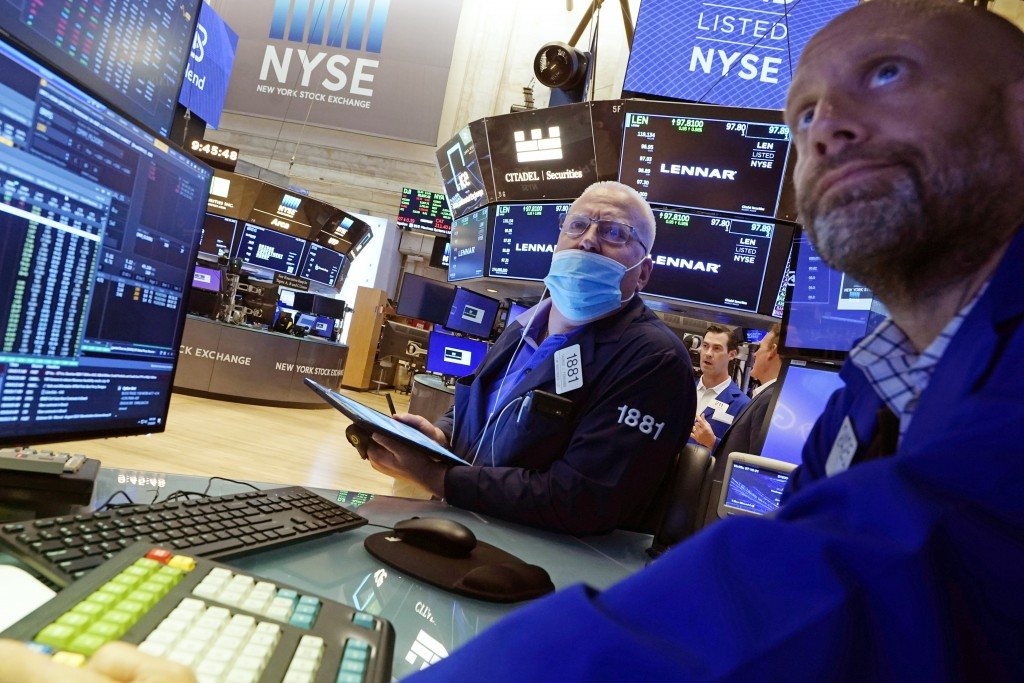 Trader Thomas Ferrigno, left, and specialist Meric Greenbaum work on the floor of the New York Stock Exchange, Friday, July 16, 2021. Stocks are off t...