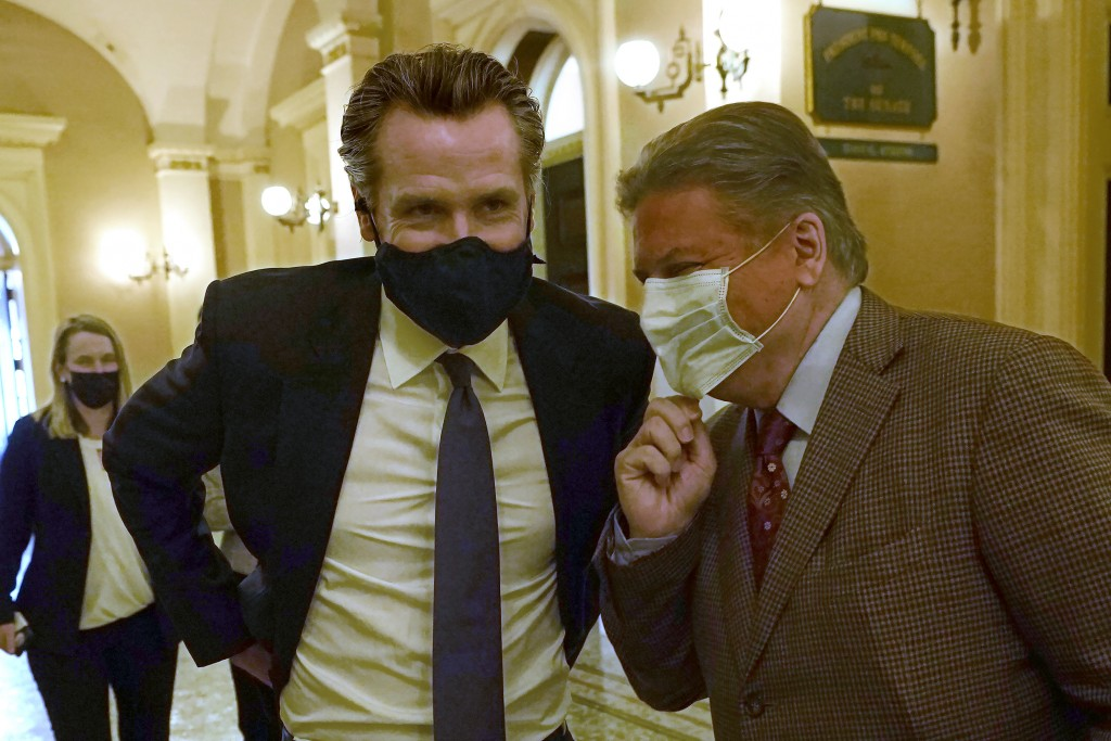 California Gov. Gavin Newsom left, talk with state Sen. Robert Hertzberg, D-Van Nuys, after lawmakers approved the nation's first state-funded guarant...