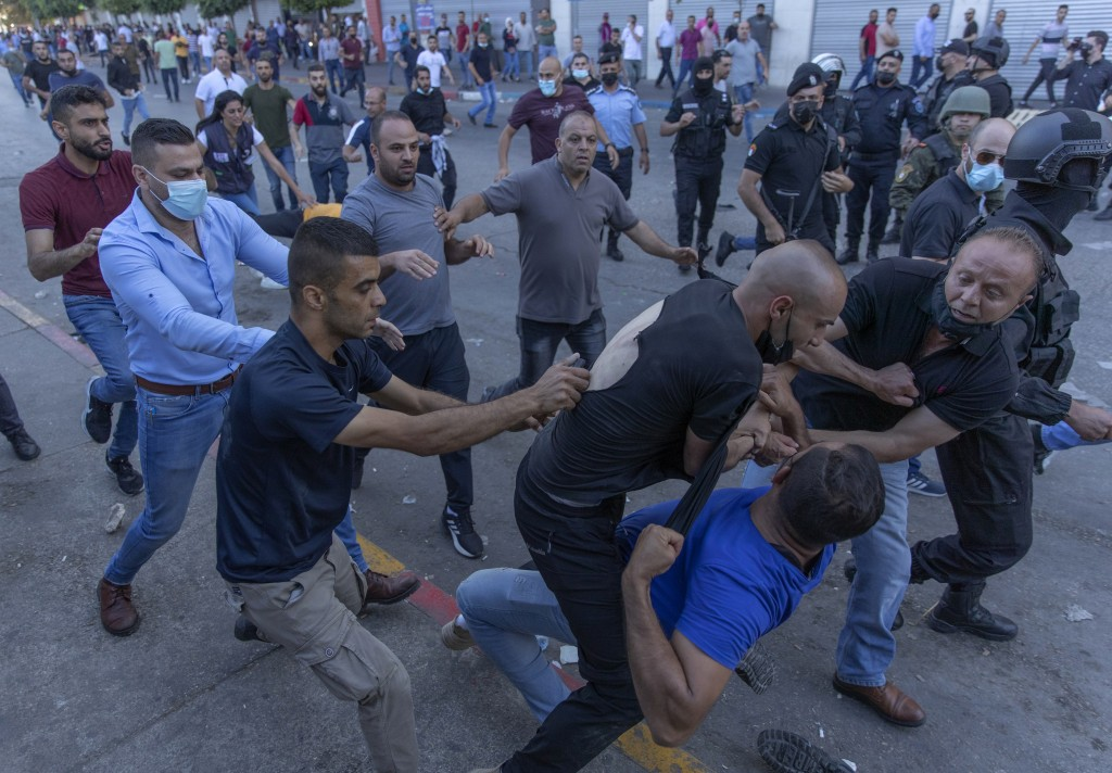 Plainclothes Palestinian security officers detain a protester during clashes that erupted during a demonstration against the death of Nizar Banat, a c...