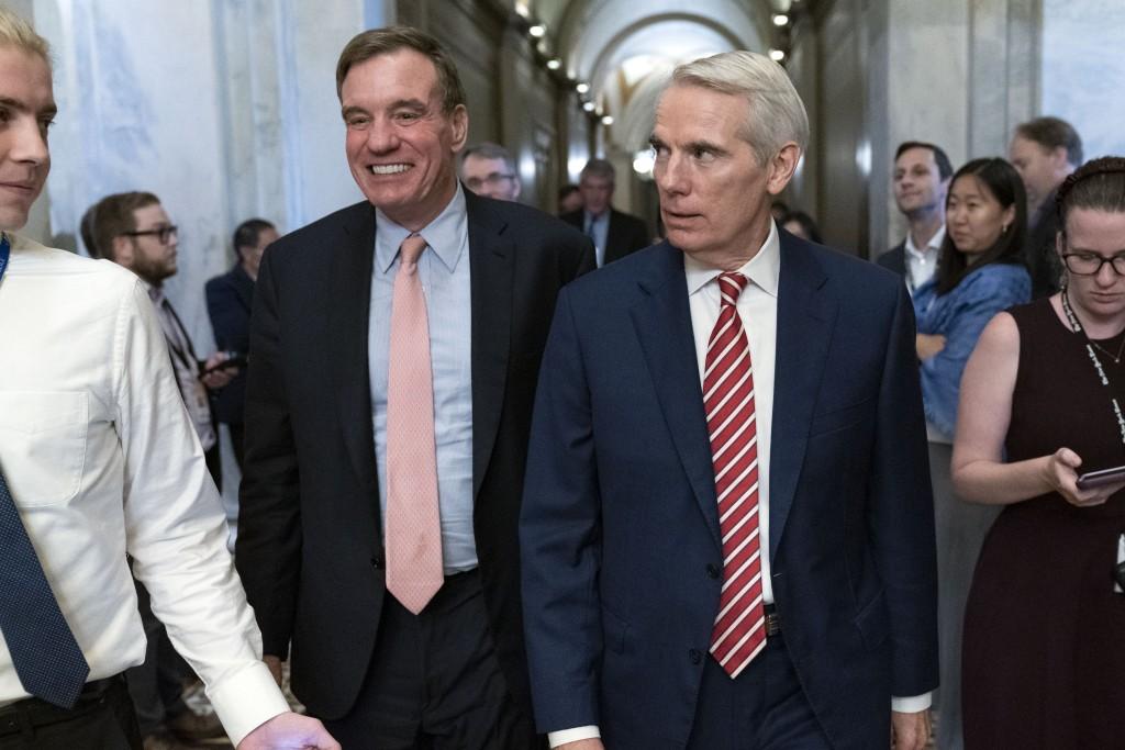 Sen. Mark Warner, D-Va., left, accompanied by Sen. Rob Portman, R-Ohio, walk for a closed door talks about infrastructure on Capitol Hill in Washingto...