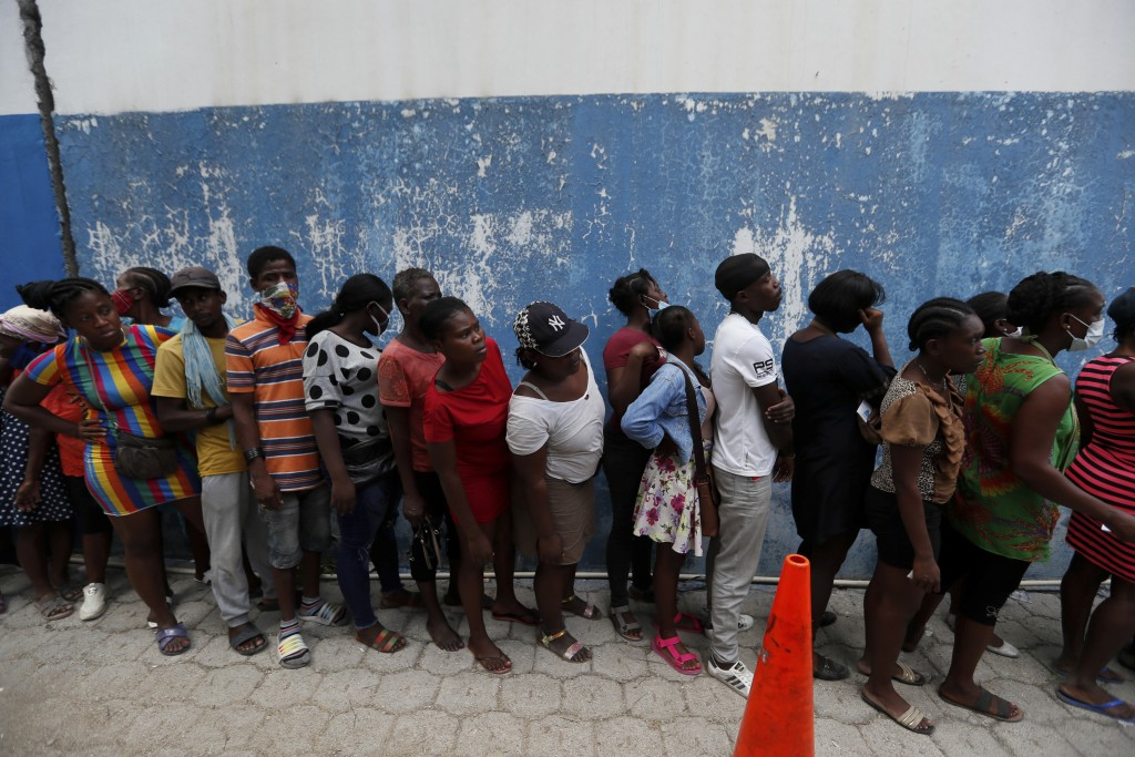 People wait for handouts of corn flour sacks distributed by World Food Program, inside of a police station in Port-au-Prince, Haiti, Thursday, July 15...