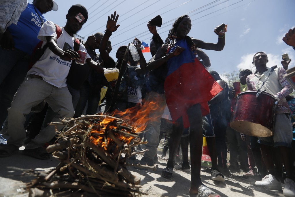 Supporters of former Haitian President Jean-Bertrand Aristide dance and drum as they wait near the airport for his expected arrival from Cuba, where h...