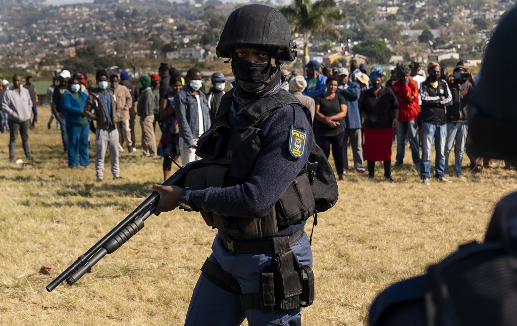 An armed policeman patrols as Police Minster Bheki Cele visits Phoenix, a neighbourhood severely affected by unrest and racial tensions near Durban, S...