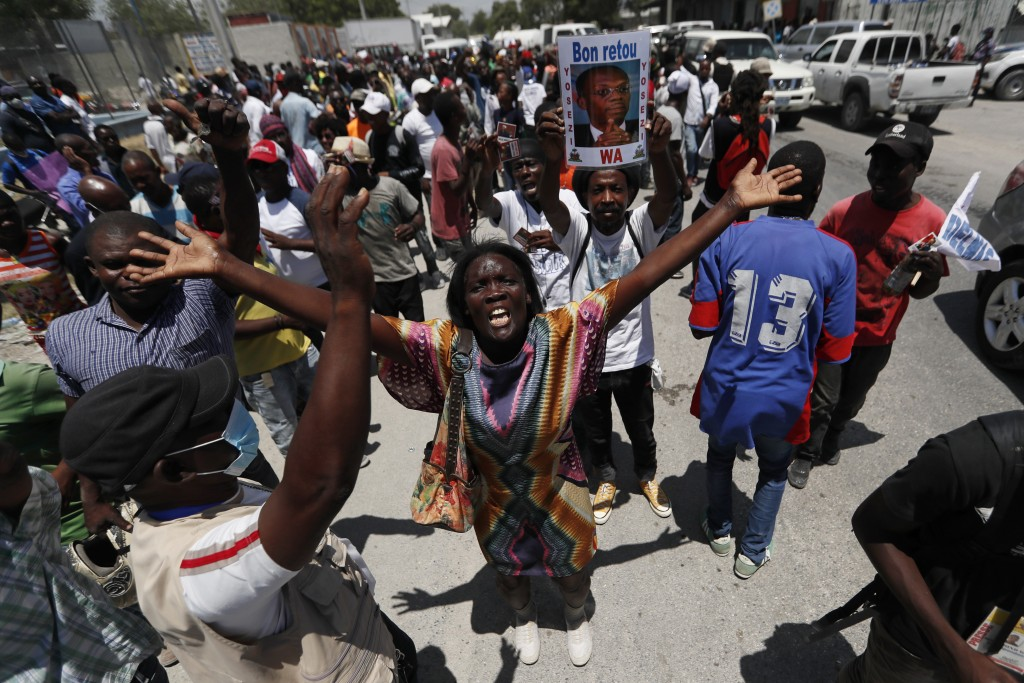 Supporters of former Haitian President Jean-Bertrand Aristide gather near the airport for his expected arrival from Cuba, where he underwent medical t...
