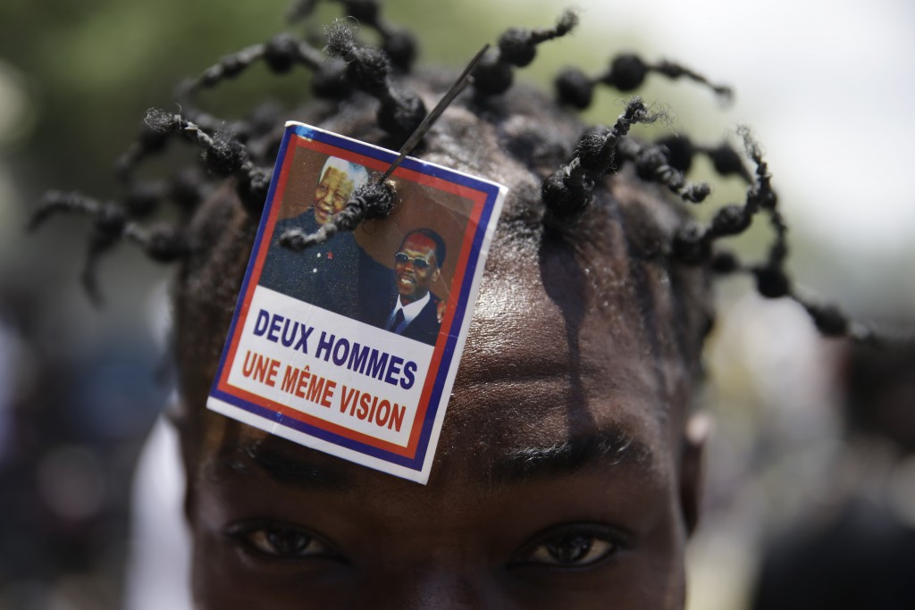 A supporter of former Haitian President Jean-Bertrand Aristide wears a photo of Aristide and late South African President Nelson Mandela as he waits n...