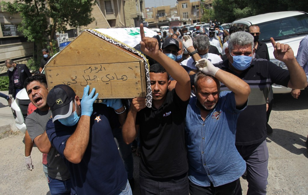 FILE - In this July 12, 2020 file photo, mourners carry the flag-draped coffin of Hisham al-Hashimi during his funeral, in the Zeyouneh area of Baghda...