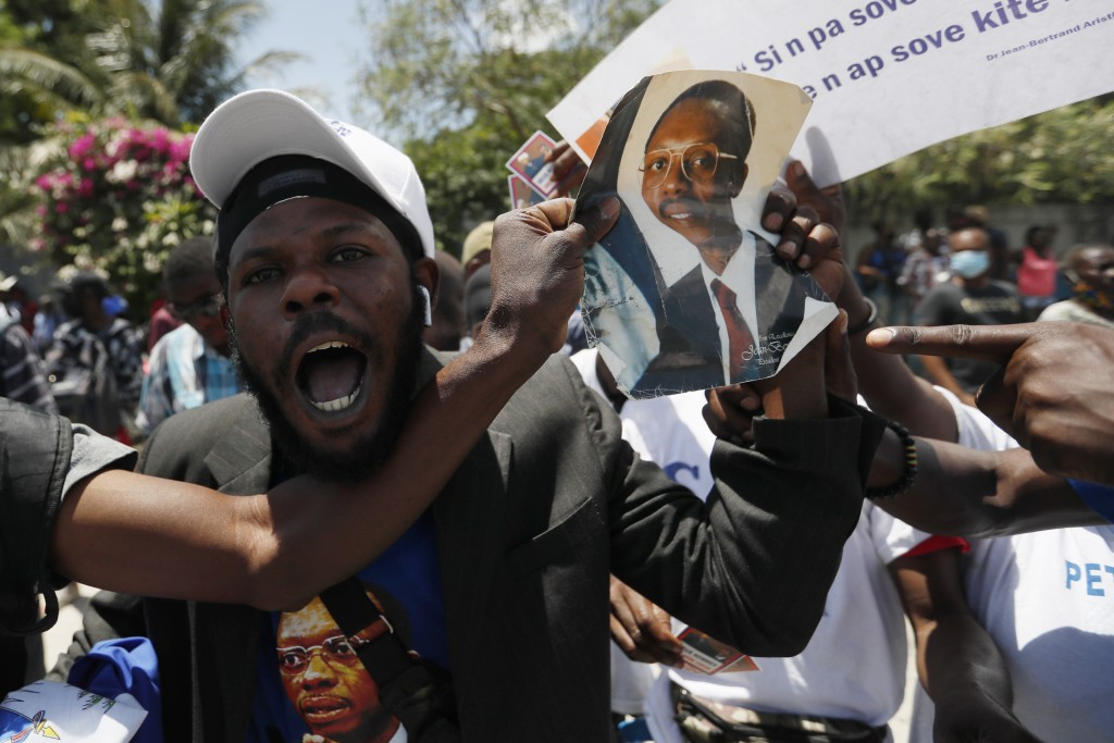 Supporters of former Haitian President Jean-Bertrand Aristide celebrate as they wait at the airport for his expected arrival from Cuba, where he under...