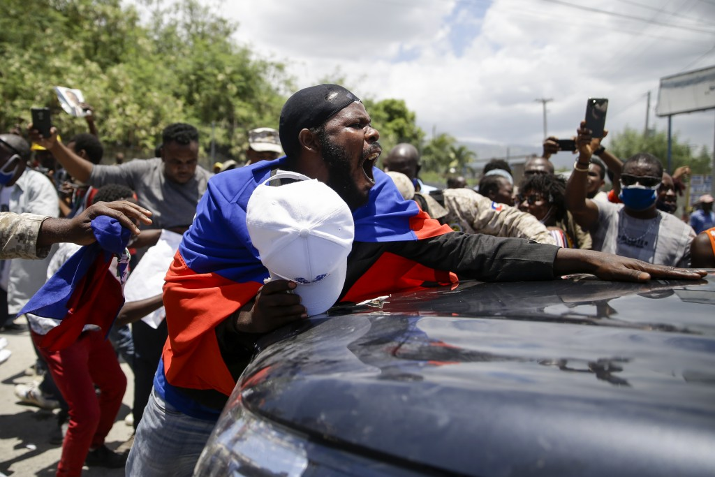 Supporters of former Haitian President Jean-Bertrand Aristide stand in front of a vehicle that is part of the caravan driving him away from the airpor...