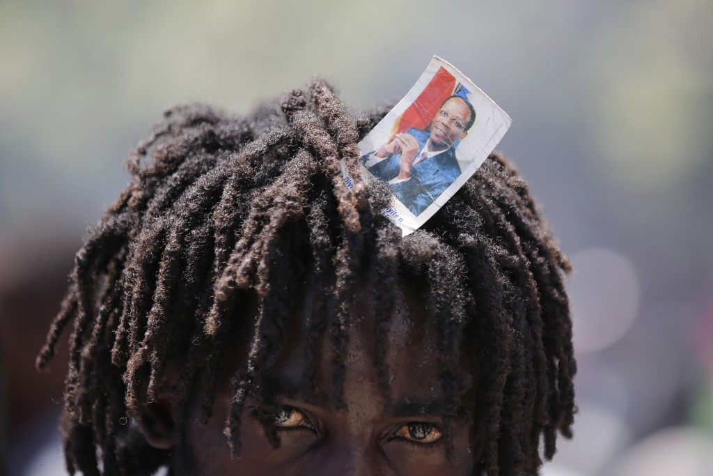 A supporter of former Haitian President Jean-Bertrand Aristide looks into the camera as he waits with others near the airport for his expected arrival...