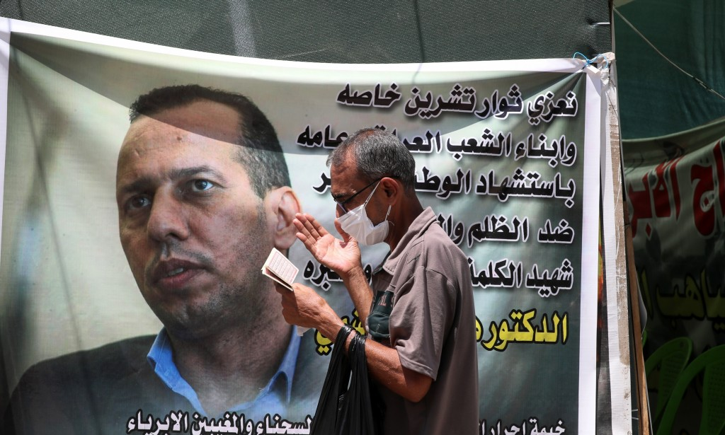 FILE - In this July 12, 2020 file photo, a protester prays by a poster showing Hisham al-Hashimi an Iraqi analyst who was a leading expert on the Isla...