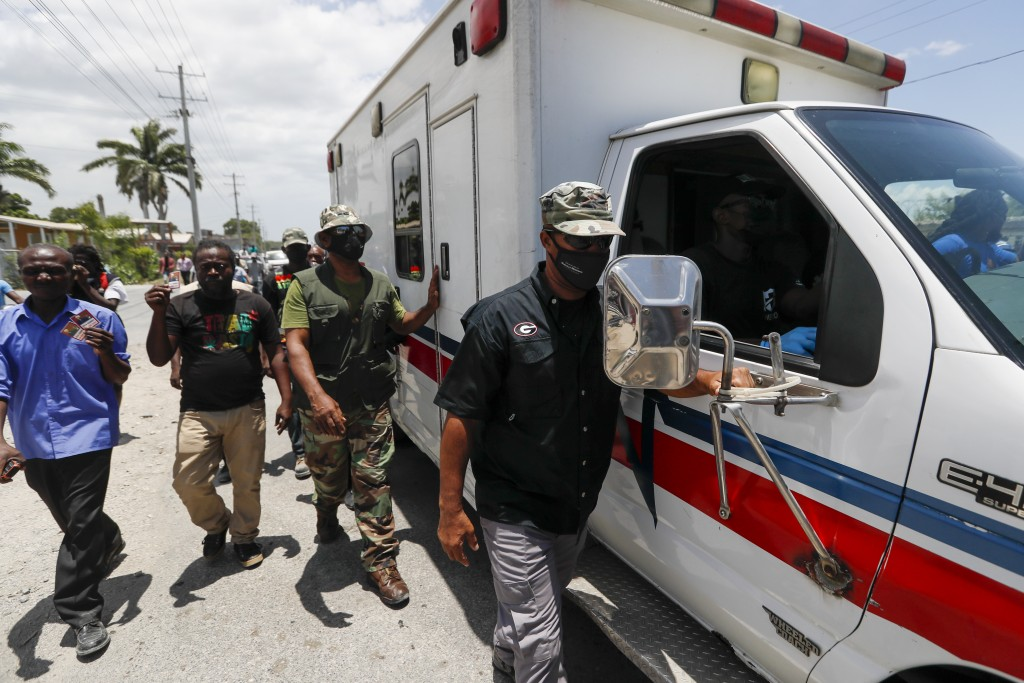 An ambulance carrying former Haitian President Jean-Bertrand Aristide leaves the airport after his arrival from Cuba, where he underwent medical treat...