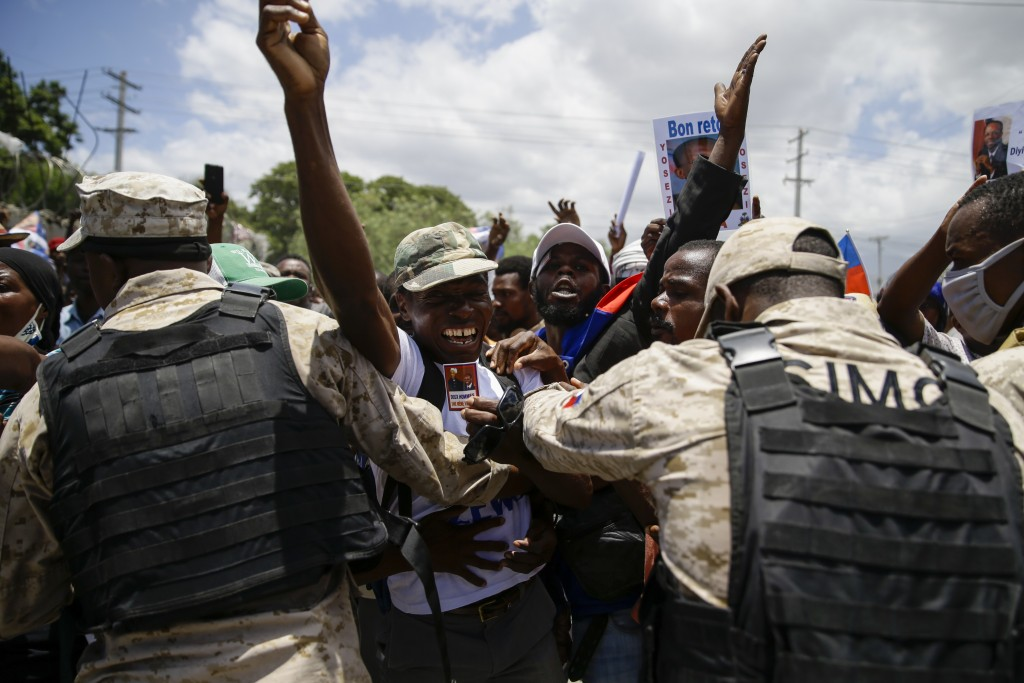 Supporters of former Haitian President Jean-Bertrand Aristide celebrate his arrival from Cuba, where he underwent medical treatment, in Port-au-Prince...