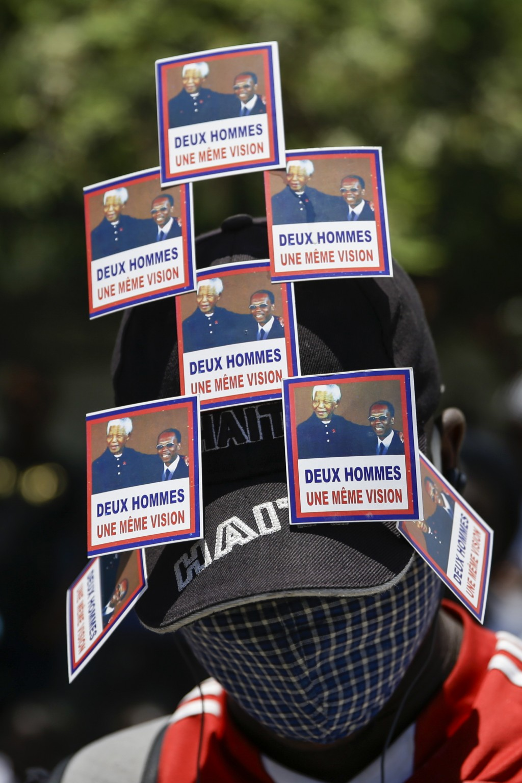 A supporter of former Haitian President Jean-Bertrand Aristide wears stickers of him and late South African President Nelson Mandela, as he awaits Ari...