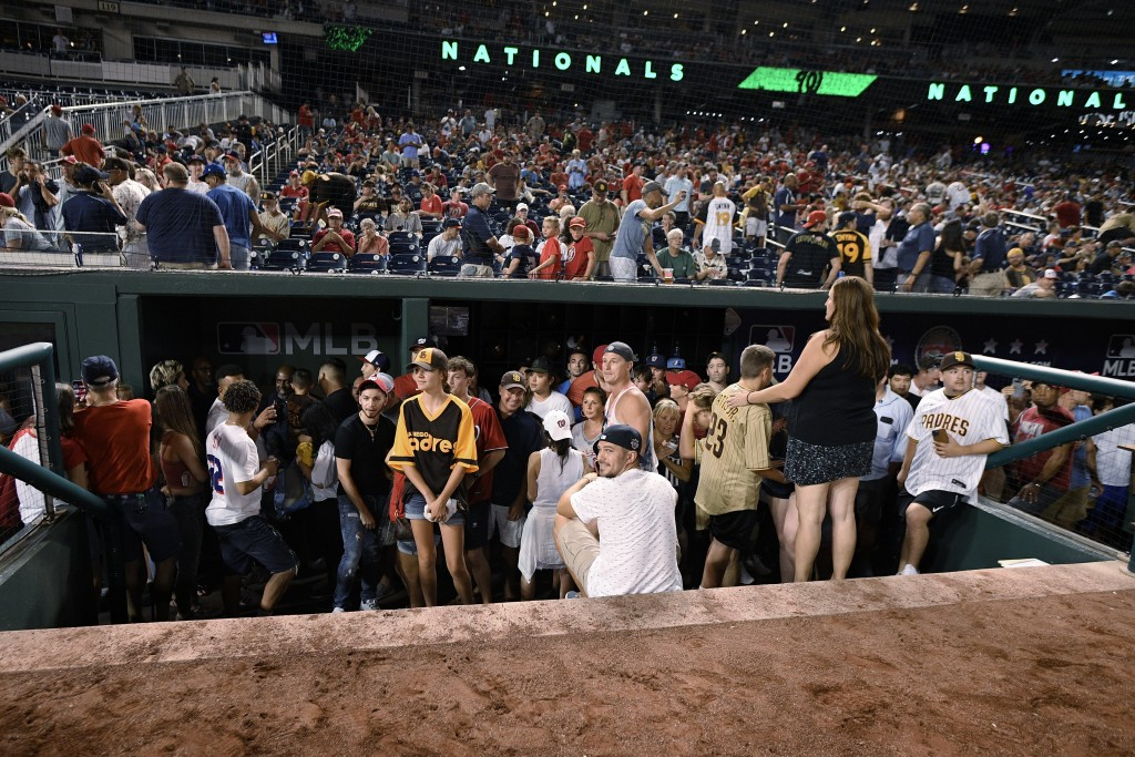 Spectators stand in the visiting team dugout during a stoppage in play due to an incident near the ballpark in the sixth inning of a baseball game bet...
