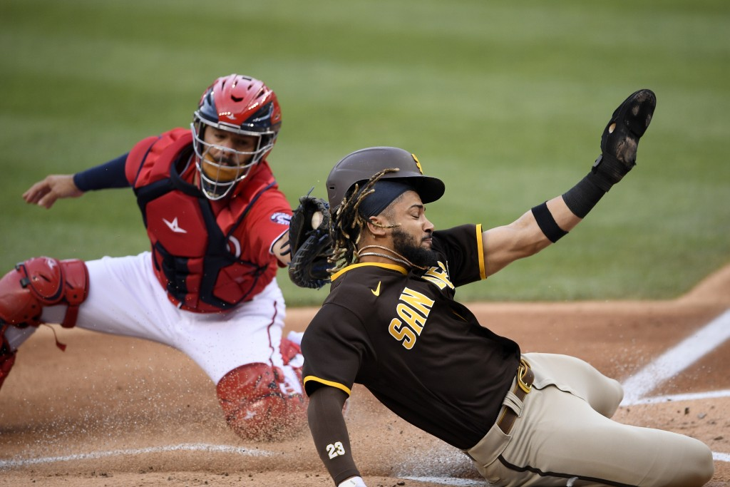 San Diego Padres' Fernando Tatis Jr., right, slides home safely to score against Washington Nationals catcher Rene Rivera on a sacrifice fly by Manny ...