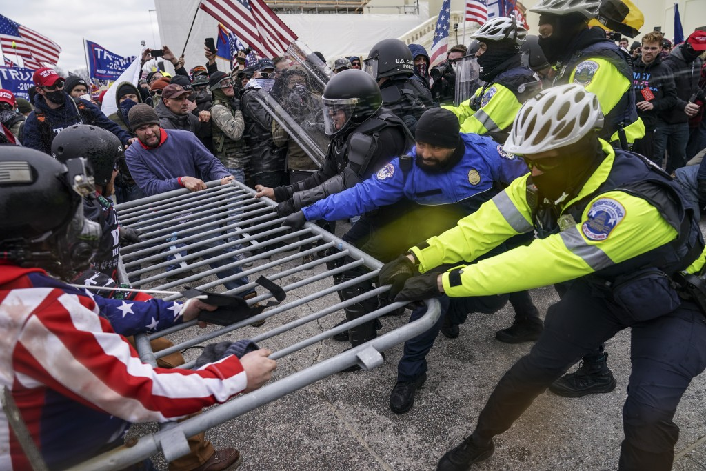 FILE - In this Jan. 6, 2021, file photo violent insurrectionists loyal to President Donald Trump hold on to a police barrier at the Capitol in Washing...