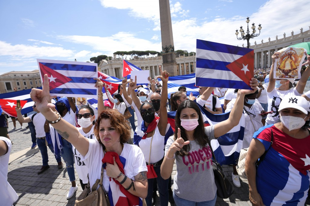 Members of Italian Cuban community show flags during Pope Francis' Angelus noon prayer from the window of his studio overlooking St. Peter's Square, a...