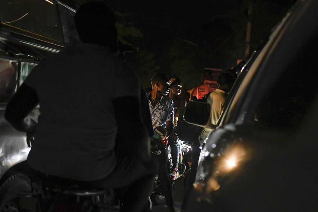 Motorcyclists waits in a long line to fill up their tanks at a gas station amid a fuel shortage in Port-au-Prince, Haiti, late Saturday, July 17, 2021...