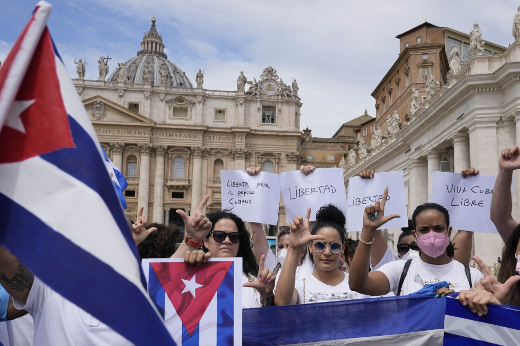 """Members of Italian Cuban community show flags and banners reading in Spanish """"freedom for Cuba"""" before Pope Francis' Angelus noon prayer from the wind..."""