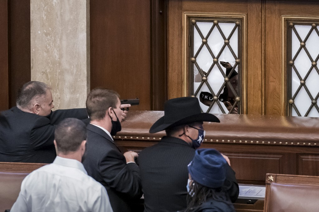 FILE - In this Jan. 6, 2021 file photo, security agents and lawmakers barricade the door to the House chamber as violent mob loyal to then-President D...