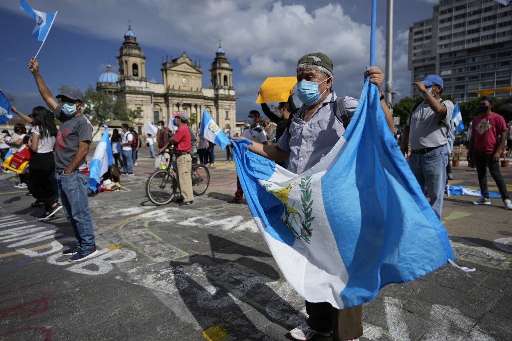 Protesters wave national flags during a rally demanding the resignation of Guatemalan President Alejandro Giammattei, claiming his government has mism...