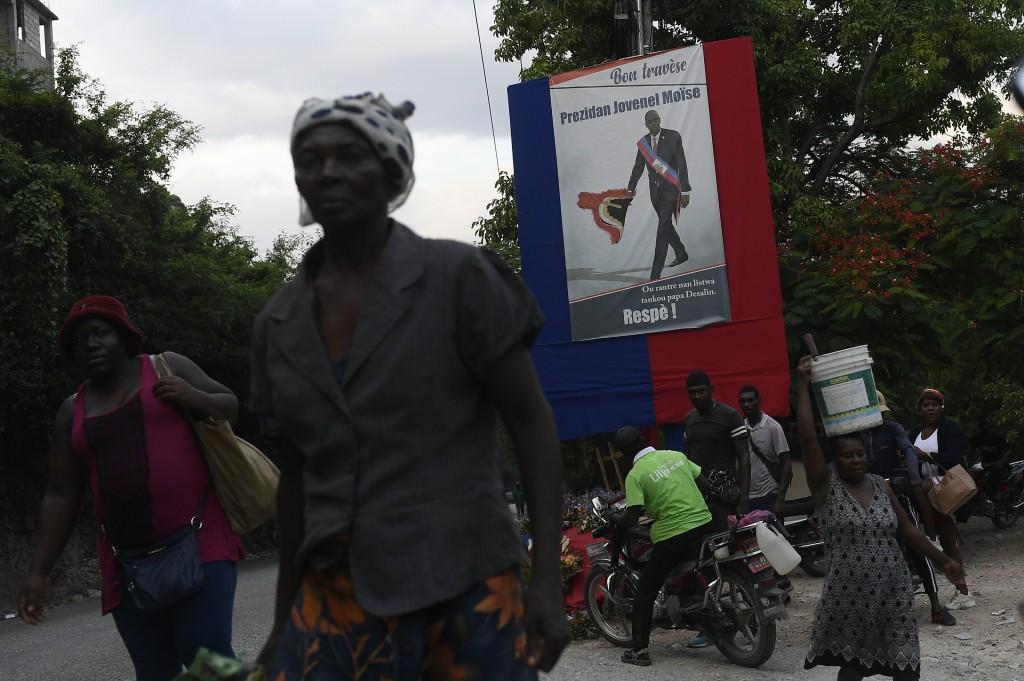 People walk near a poster featuring President Jovenel Moise in Port-au-Prince, Haiti, Saturday, July 17, 2021, ten days after Moise was assassinated i...