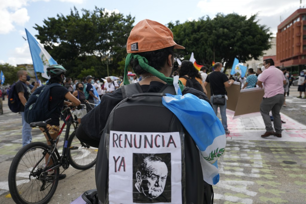 A woman wears a poster on her back with a message demanding the resignation of Guatemalan President Alejandro Giammattei, during a demonstration in wh...