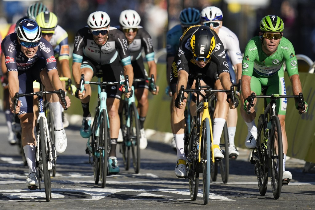 Belgium's Wout Van Aert, second left, crosses the finish line to win ahead of Britain's Mark Cavendish, wearing the best sprinter's green jersey, righ...