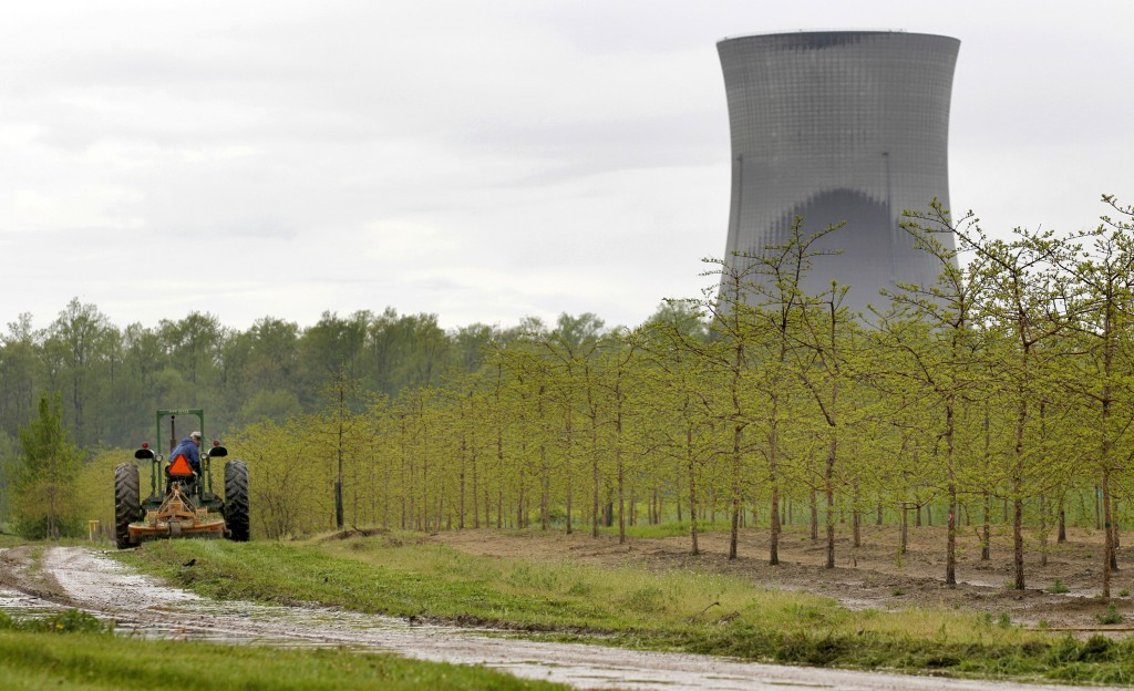FILE - In this May 18, 2011, file photo, a worker drives a tractor through a tree farm in North Perry, Ohio, near the cooling towers of the Perry Nucl...