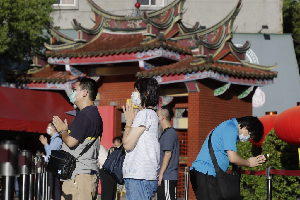 People wear face masks to protect against the spread of the coronavirus and pray outside Hsing Tian Kong Temple in Taipei, July 19, 2021.