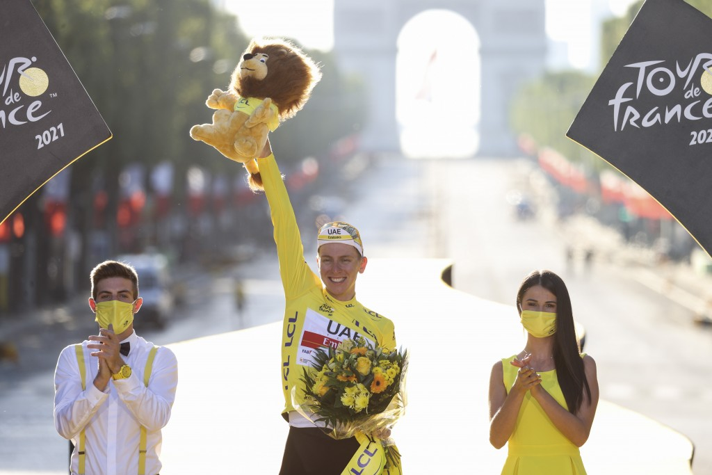 Tour de France winner Slovenia's Tadej Pogacar, wearing the overall leader's yellow jersey, celebrates on the podium after the twenty-first and last s...