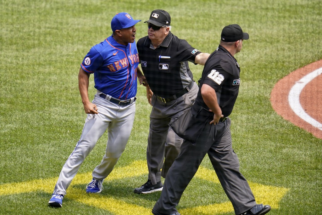 New York Mets manager Luis Rojas, left, is separated from umpire Jeremy Riggs (112) by umpire crew chief Larry Vanover, center, during the first innin...