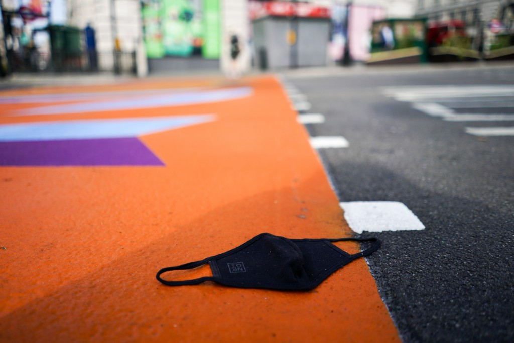 A face mask lies on the ground at Piccadilly Circus in central London, Monday, July 19, 2021. As of Monday, face masks are no longer legally required ...