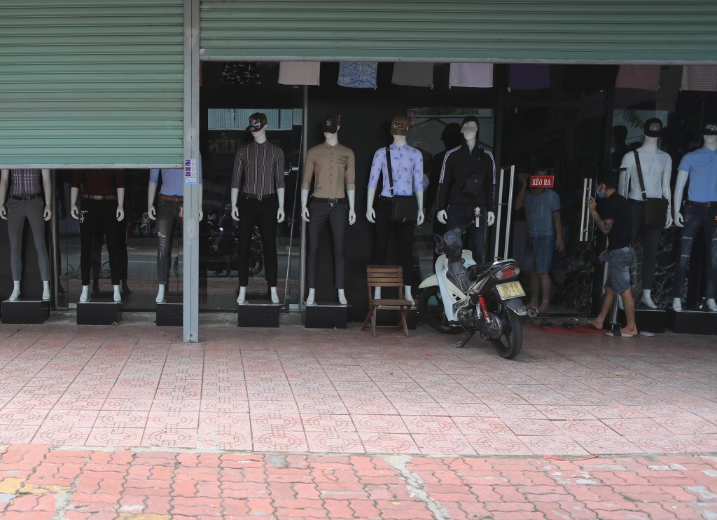 People enter a closed clothing shop in Vung Tau, Vietnam Monday, July 19, 2021. Southern Vietnam, with a population of nearly 40 million people, start...