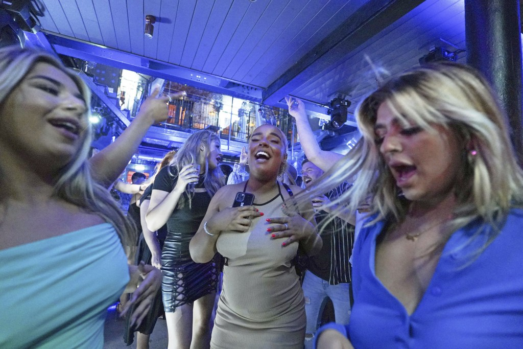 People dance in Bar Fibre in Leeds, after the final legal coronavirus restrictions were lifted in England at midnight Monday July 19, 2021. (Ioannis A...