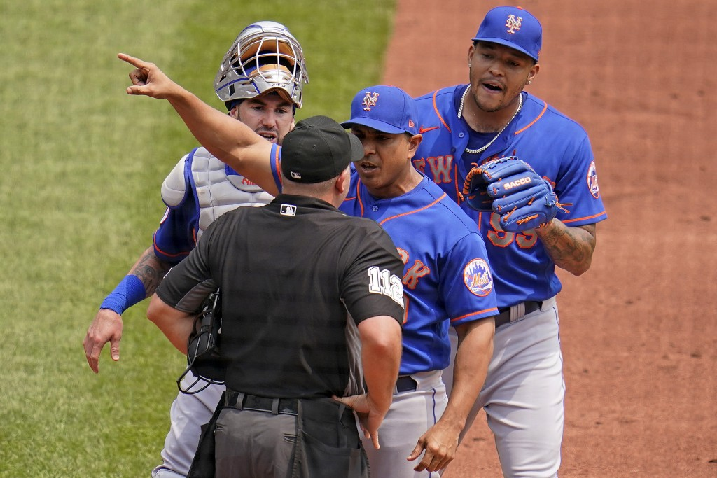 New York Mets manager Luis Rojas, center, makes his point to umpire Jeremy Riggs (112) with catcher Tomas Nido, left rear, and starting pitcher Taijua...