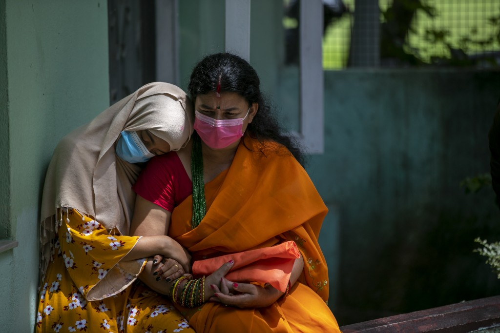 A physically disabled Nepalese girl waits with her mother to receive a dose of Johnson and Johnson vaccine at the Nepal Disabled Association Khagendra...