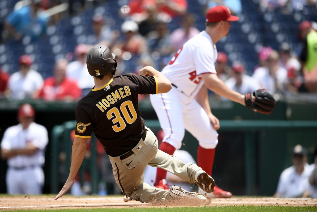 San Diego Padres' Eric Hosmer (30) starts his slide toward home to score on a single by Tommy Pham as Washington Nationals relief pitcher Sam Clay, ri...