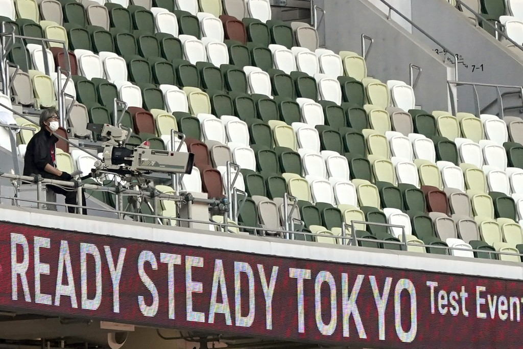 A TV cameraman sits beside empty spectators' seats during an athletics test event for Tokyo 2020 Olympics Games at the National Stadium, in Tokyo, Jap...