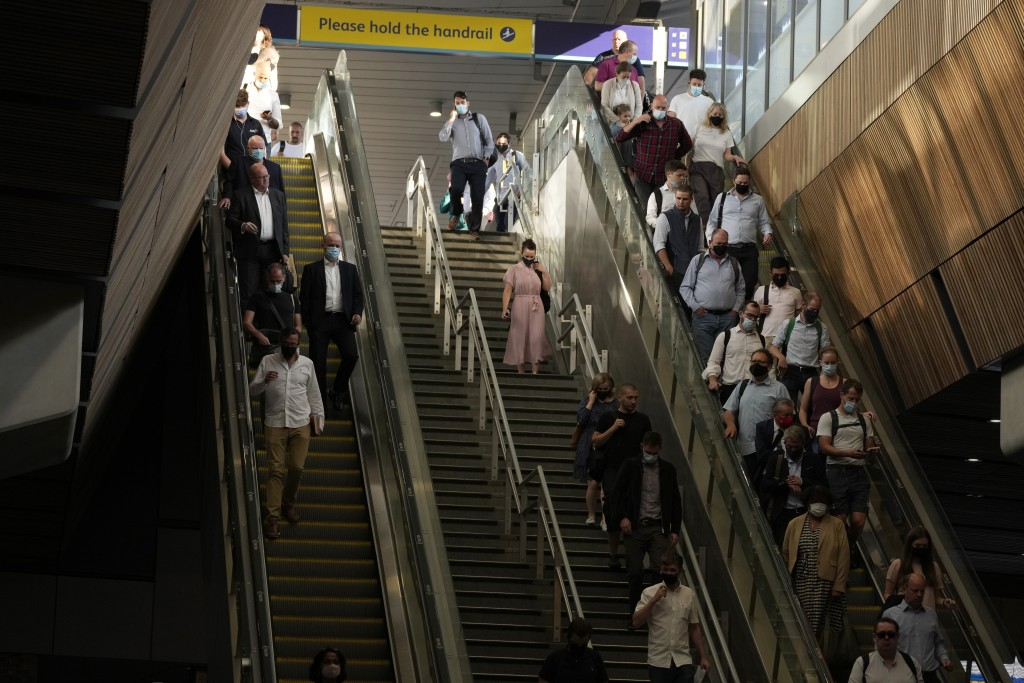 """On what some have called """"Freedom Day"""", marking the end of coronavirus restrictions in England, commuters take escalators and stairs after disembarkin..."""
