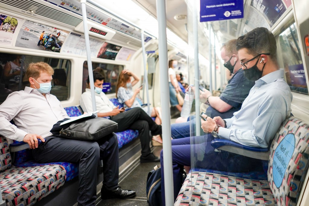 People sit on an Underground train, in London, Monday, July 19, 2021. As of Monday, face masks are no longer legally required in England, and with soc...