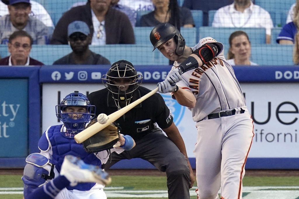 San Francisco Giants Buster Posey, right, hits a two-run home run as Los Angeles Dodgers catcher Will Smith, left, and home plate umpire Jeremie Rehak...