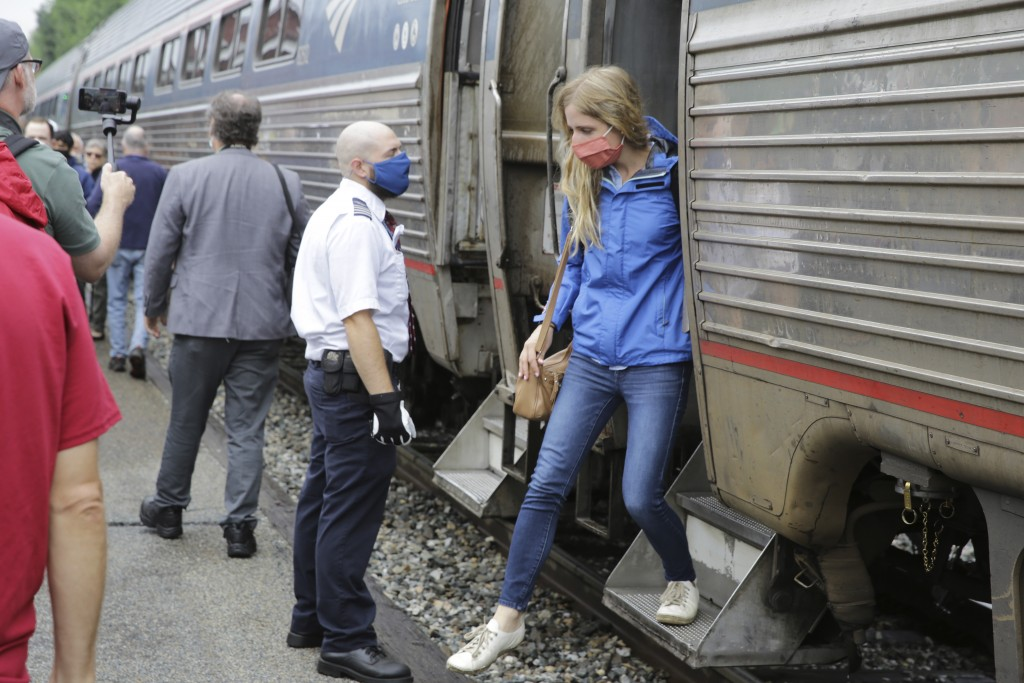A passenger, right, gets off the Amtrak Vermonter passenger train after it arrived at the Montpelier station, in Berlin, Vt., Monday July 19, 2021. Ce...